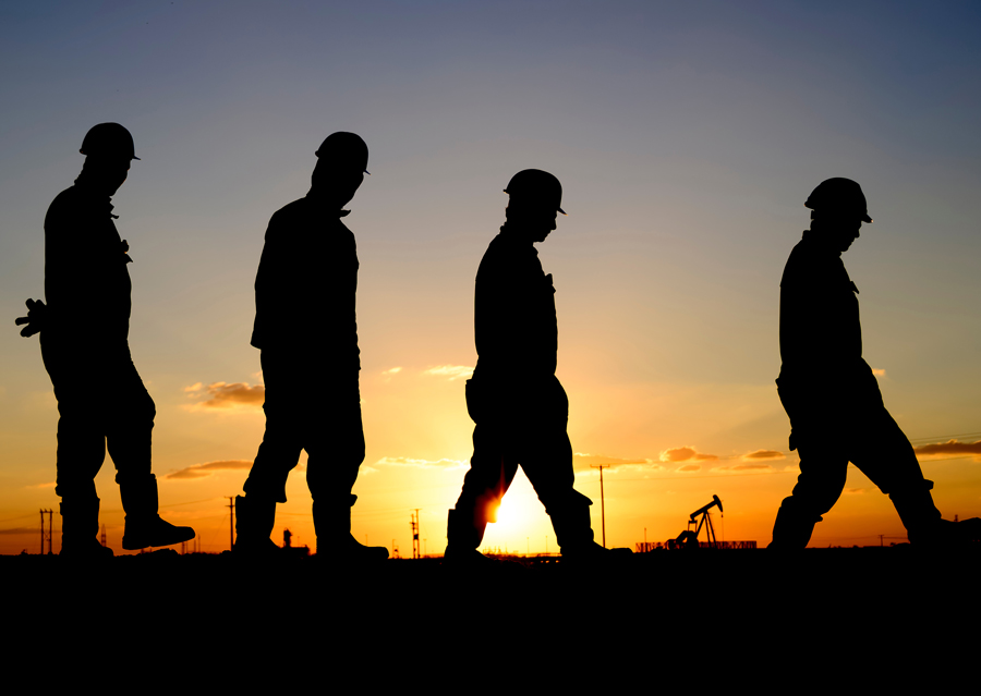 Oil workers walking in the sunset